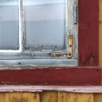 Red window frame, ochre building, rusty brace on building in Røros, Norway