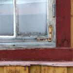 Red window frame, ochre building, rusty brace on building in Røros, Norway