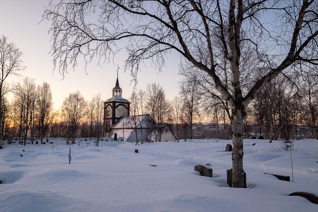snowy churchyard with church and sunrise