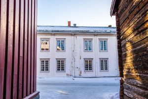 View of the Røros, Norway city hall from an alley lined with red wood buildings.